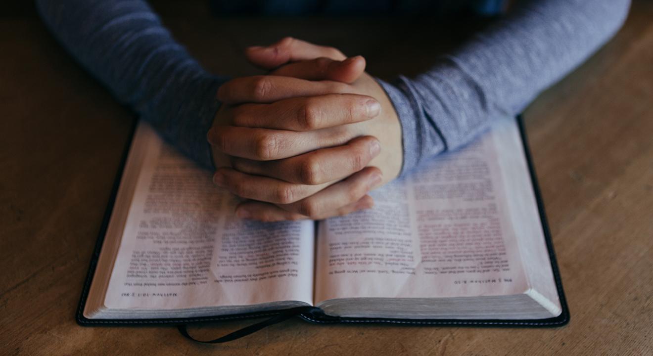 praying hands on Bible image