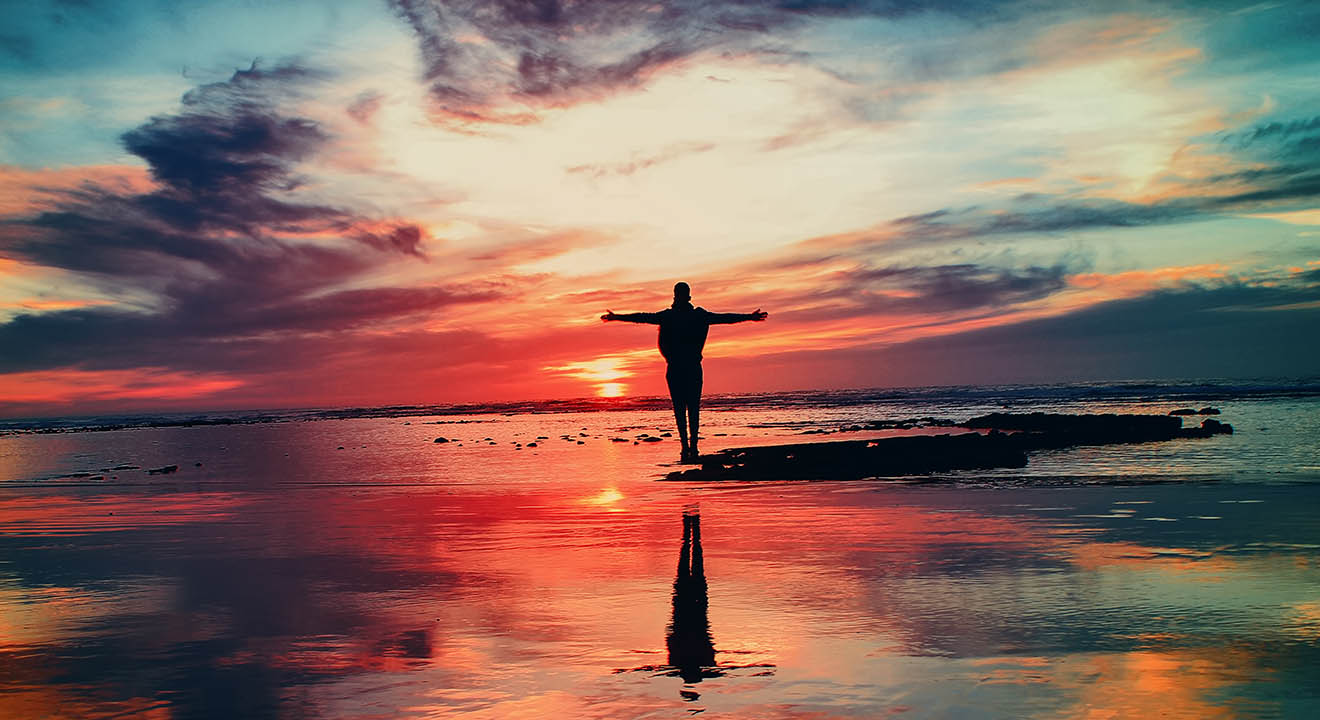 image of person looking into sunset with outstretched arms