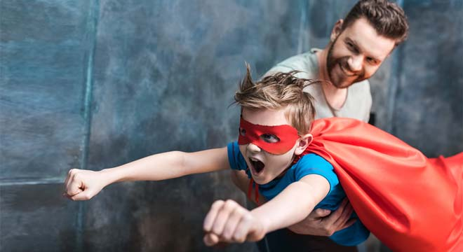 superhero son flying in dad's arms